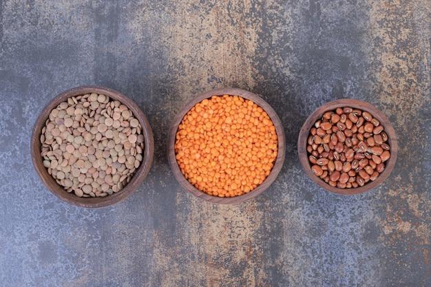 大理石の表面に生豆とレンズ豆の3つの木製ボウル。