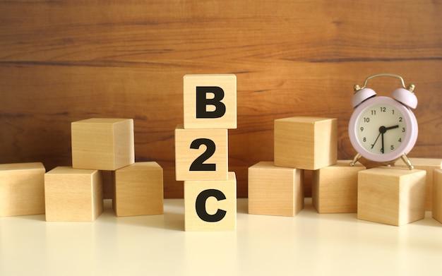 갈색 배경에 수직으로 쌓인 세 개의 나무 큐브가 b2c라는 단어를 구성합니다.