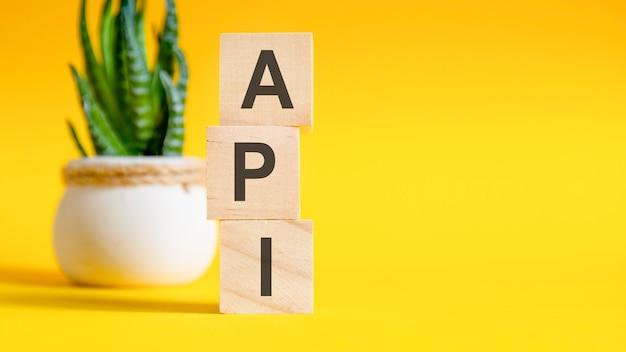文字付きの3つの木製の立方体-api、黄色のテーブル、右側のテキスト用のスペース。正面図の概念、背景に花。 api-アプリケーションプログラミングインターフェイスの略