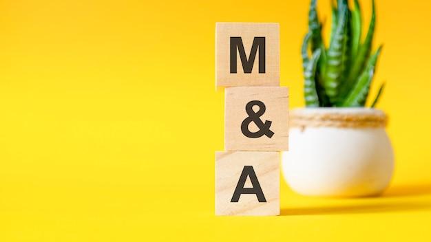 노란색 테이블에 m과 a라는 글자가 있는 세 개의 나무 큐브, 오른쪽에 텍스트를 위한 공간. m과 a - mergers and acquisitions의 줄임말입니다. 전면 보기 개념, 백그라운드에서 꽃