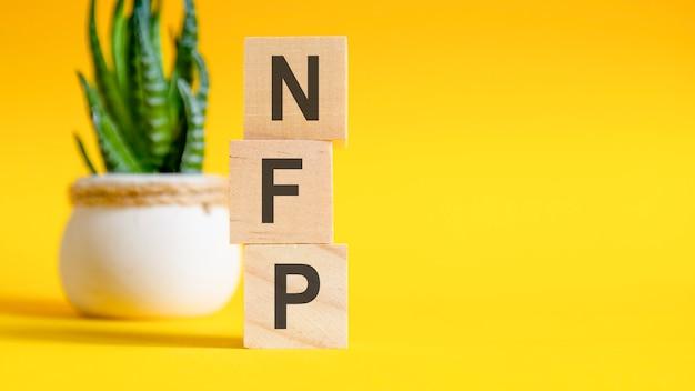 문자가 있는 3개의 나무 큐브 - nfp, 노란색 테이블, 오른쪽에 텍스트를 위한 공간. 전면 보기 개념, 백그라운드에서 꽃입니다. nfp - non-farm payroll의 약자