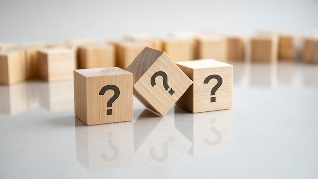 Three wooden cubes with question marks over a grey background with copy space.