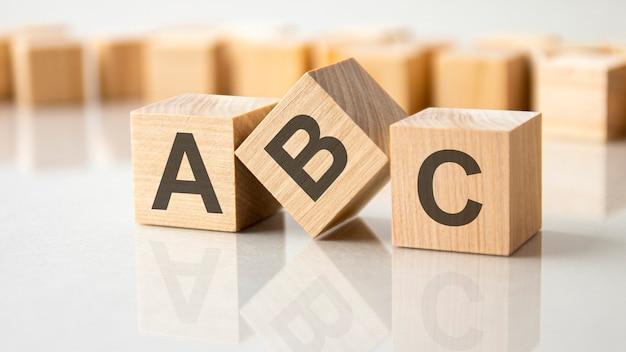 회색 테이블의 밝은 표면에 abc라는 글자가 있는 세 개의 나무 큐브, 비즈니스 개념