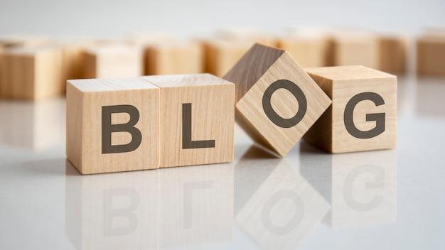 회색 테이블의 밝은 표면에 blog라는 글자가 있는 세 개의 나무 큐브. 큐브의 비문은 테이블 표면에서 반사됩니다. 비즈니스 개념입니다.