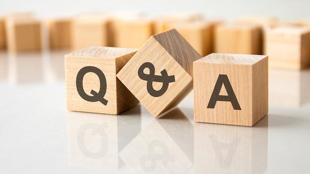 灰色のテーブルの明るい表面にqとaの文字が付いた3つの木製の立方体、ビジネスコンセプト
