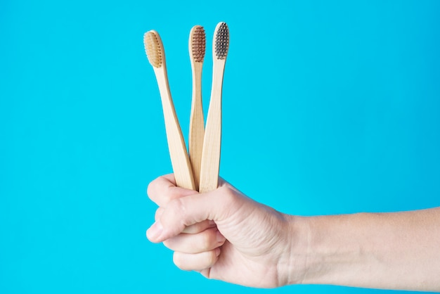 Three wooden eco friendly bamboo toothbrushes on a blue background. dental care conept