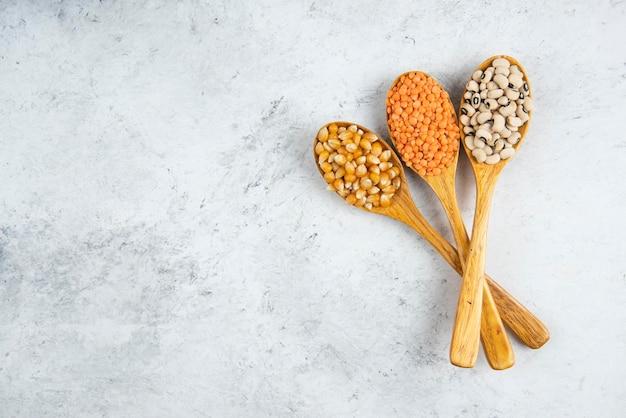 Tre cucchiai di legno di fagioli crudi su un tavolo di marmo.