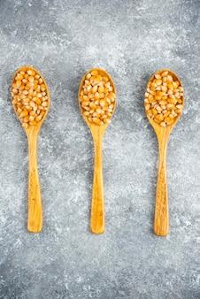 Tre cucchiai di legno di semi crudi sulla superficie di marmo.
