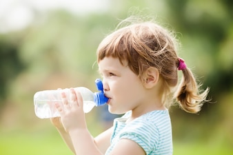 Three year child drinking from  bottle