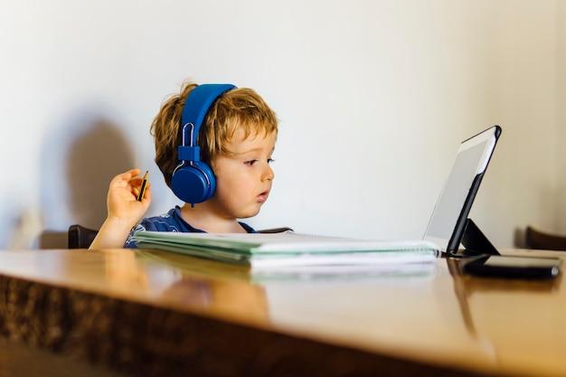 Трехлетний мальчик, посещающий онлайн-класс в школе, подключенный к планшету дома, смотрит сми