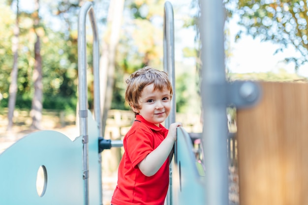Three year old boy enjoying an afternoon after school games at a playground in a park