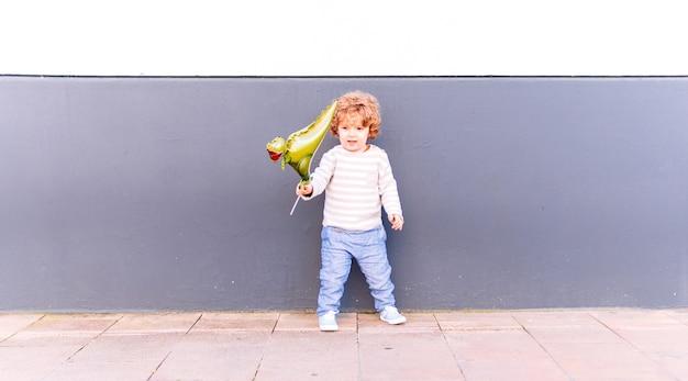 春または夏の日没時に風船で遊ぶ白と灰色の壁にもたれて3歳の少年