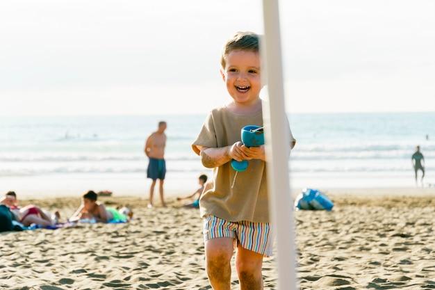 夏のビーチで砂遊びをする3歳の男の子