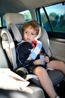 Three year old boy sitting in car safety seat going to school in the morning
