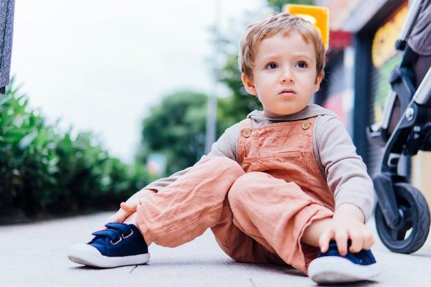 通りの地面に座っている3歳の少年