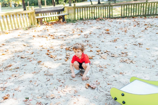 Three year old boy sitting squat resting on the sand and dry leaves in a playground