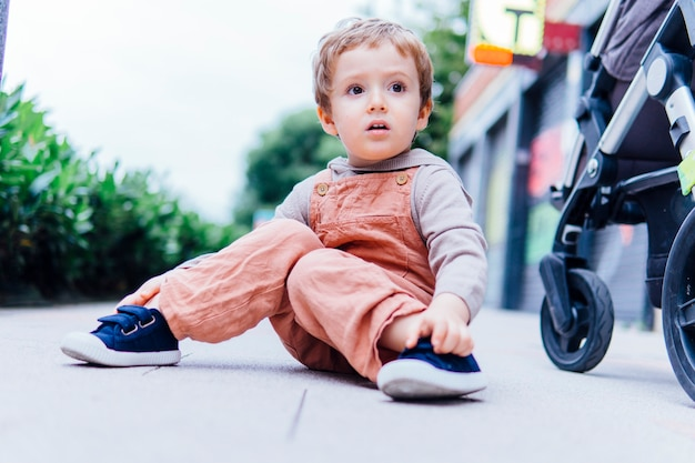 Three year old boy with surprised gesture sitting in the street on a cool day