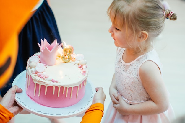 Three years old blonde adorable girl in a pink dress blowing candles on birthday pink cake with number three