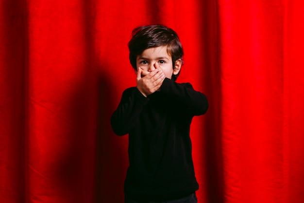 Трехлетний мальчик, одетый в черную одежду, закрывает рот на фоне красной занавески.