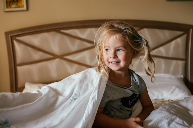 Three years old shaggy white girl sitting on a bed covered with a blanket and smiling