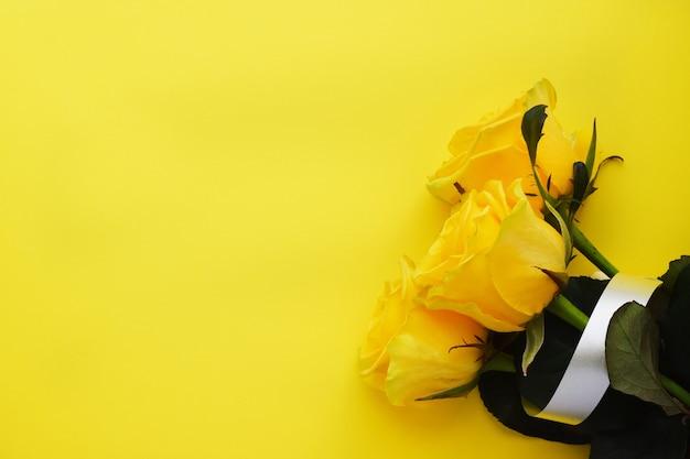 Три желтых красивых розы на желтой стене.