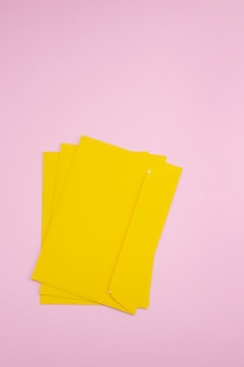 Три желтых конверта на розовом фоне
