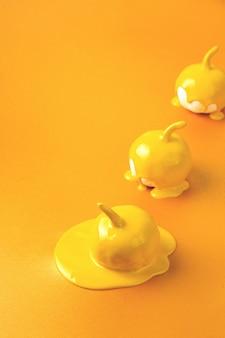 Три желтых тыквы на хэллоуин с жидкой краской, струящейся минимальной концепцией праздничного сезона