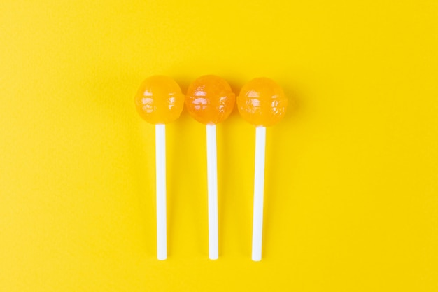Three yellow lollipops on a bright yellow background.