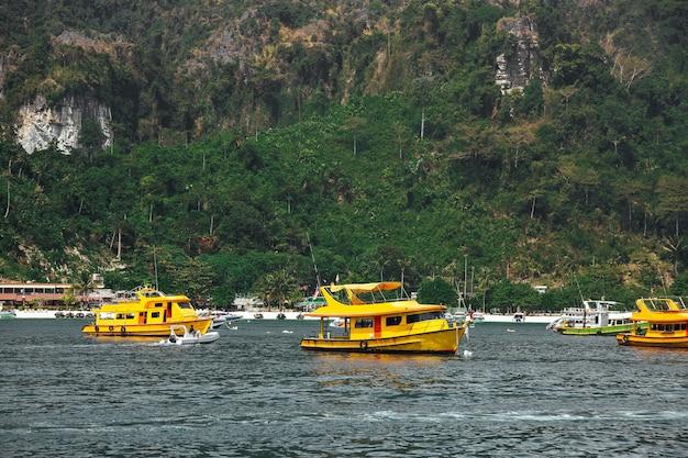 해변 근처에서 순항하는 세 명의 노란색 승객 관광 쾌속정 바다 택시