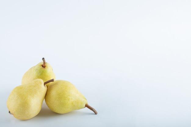 Tre pere gialle su bianco.