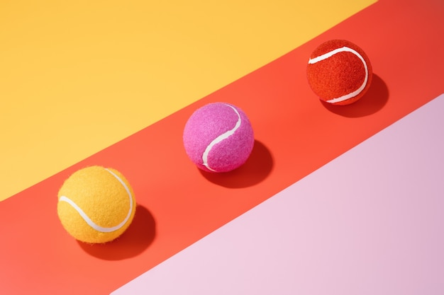 Three yellow, pink and orange tennis balls on a colourful background.sport.abstract.3d illustration
