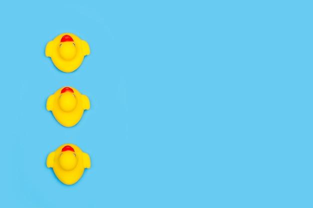 Три желтые резиновые игрушечные утки, изолированные на синем