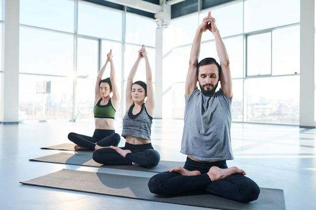 Three young active people doing yoga exercise on mats with their arms raised over heads and legs crossed