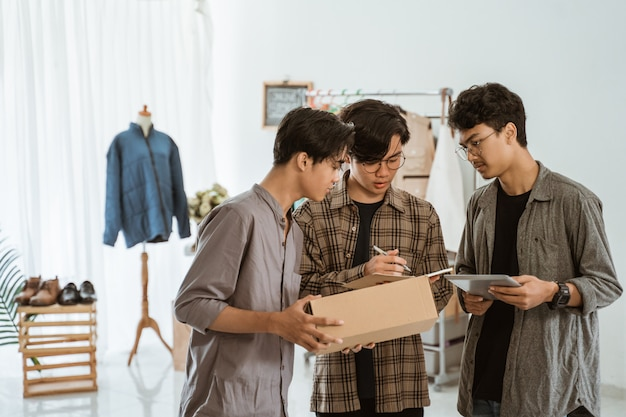 Three young asian businessman chatting about packaging of their clothing product