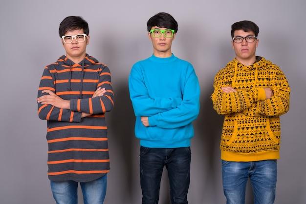 회색 벽에 함께 세 젊은 아시아 친구