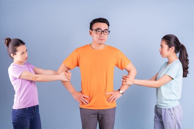 Трое молодых азиатских людей позируют на синем фоне