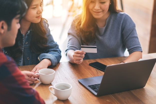 Three young asian people use credit card for purchasing and shopping online
