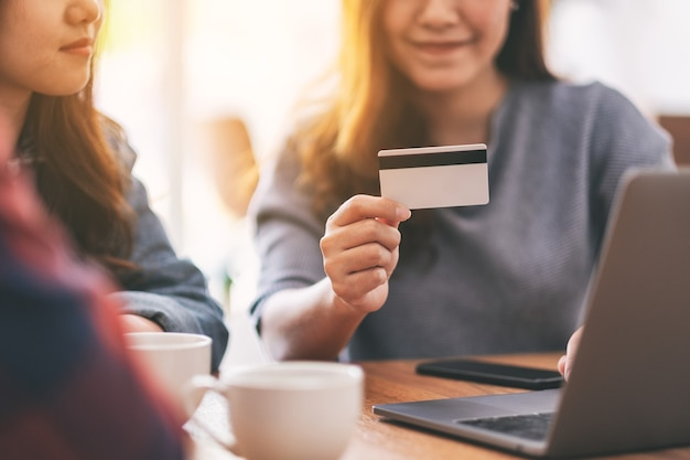 Three young asian people use credit card to purchasing and shopping online