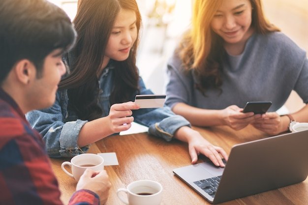 Трое молодых азиатских людей используют кредитную карту для покупок и покупок в интернете