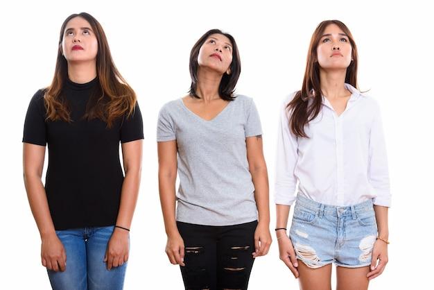 Трое молодых азиатских подруг смотрят вверх изолированные