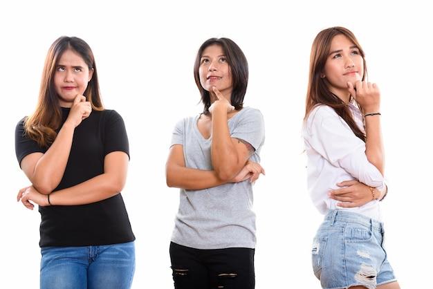 Трое молодых азиатских подруг думают, глядя вверх