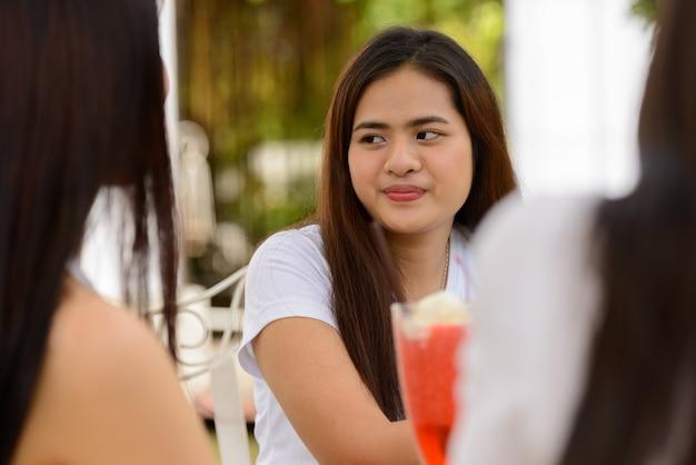 屋外の喫茶店で一緒にリラックスする友達として3人の若いアジアの女性
