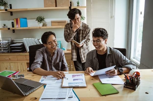 3人の若いアジア人労働者が彼らの製品についてチャット