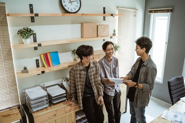 Three young asian worker chatting about their product