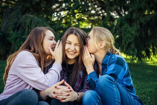 공원에서 푸른 잔디에 앉아 비밀을 공유하는 세 젊은 매력적인 여자. 쾌활한 여자 친구 험담과 속삭임 야외.
