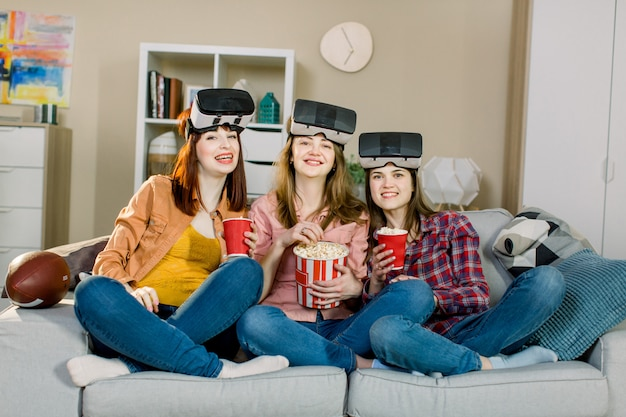 Three young attractive woman wearing headset vr virtual reality vision goggles, having party at home, eating popcorn