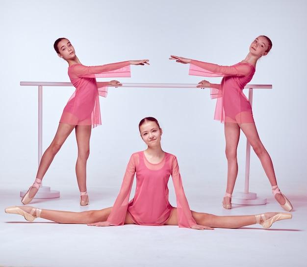 ベージュの背景のバーに伸びるピンクのドレスを着た3人の若いバレリーナ