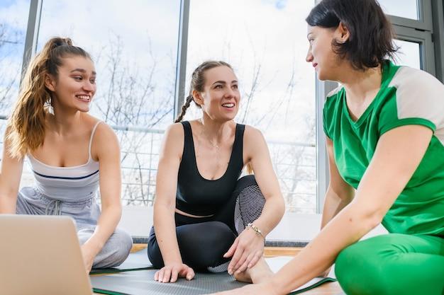 Три молодые красивые девушки фитнес-тренера, студенты сидят на полу с открытым ноутбуком и обсуждают упражнения