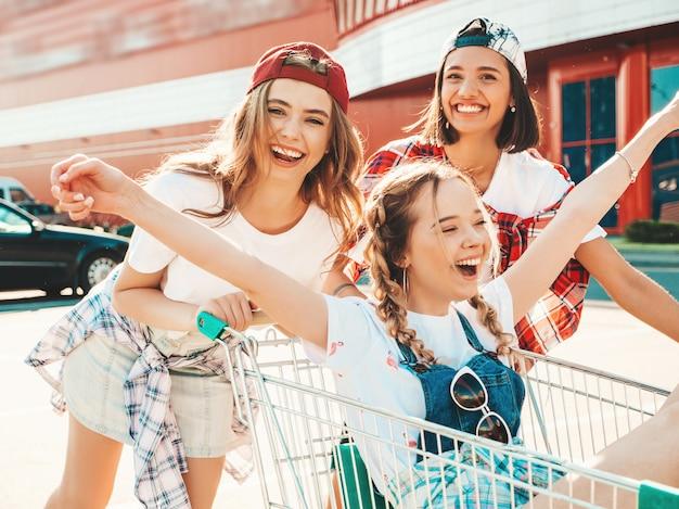 Tre giovani belle ragazze divertirsi nel carrello della spesa