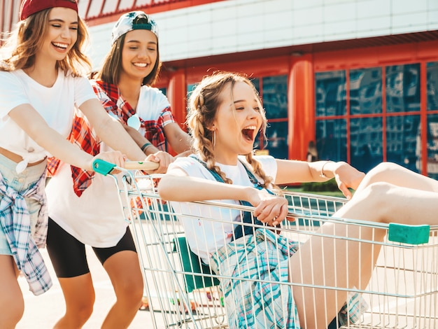 Three young beautiful girls having fun in the grocery cart